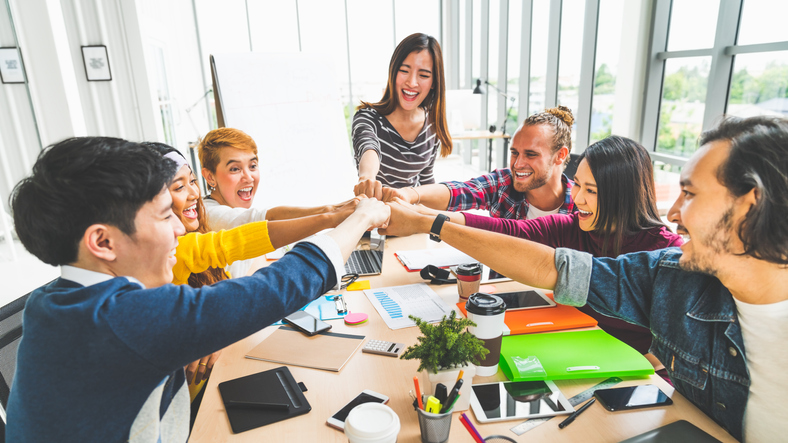 Multiethnic diverse group office coworker, business partner join hands by fist bump in modern creative office. Colleague partnership teamwork, startup company, or project achievement celebrate concept