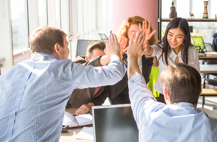 Business people happy showing team work and giving five after signing agreement or contract with foreign partners in office interior. Happy people smiling. Agreement or contract concept.
