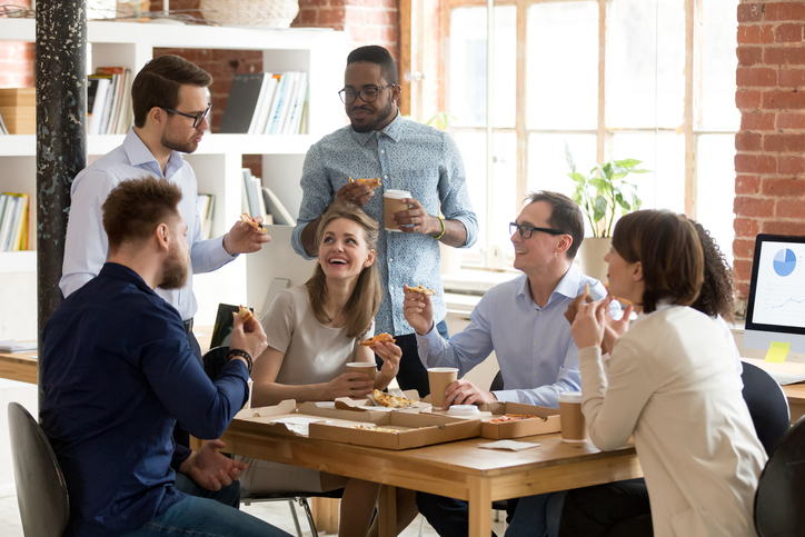 Multiracial happy work team eating pizza, drinking coffee together on break at shared workspace, having good conversation during lunch, laughing at funny joke, enjoying tasty Italian fast food