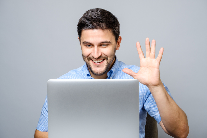 Happy young man video chatting on laptop computer isolated on gray background